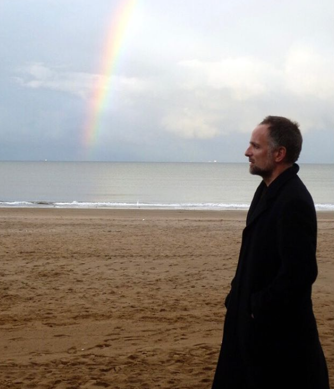 Man side profile wearing black coat on sandy beach with rainbow and sea in background
